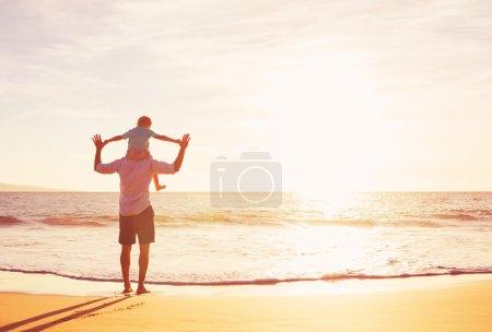 Photo pour Père et fils jouant sur la plage au coucher du soleil - image libre de droit