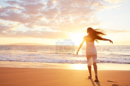 Photo for Happy carefree woman dancing at sunset on the beach. Happy free lifestyle concept. - Royalty Free Image
