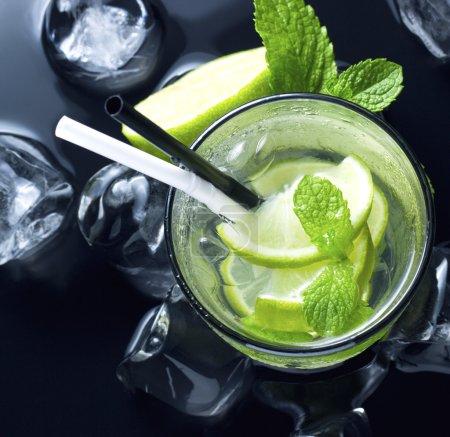 Photo pour Cocktail froid Mojito au citron vert frais, menthe et glace sur table noire - image libre de droit