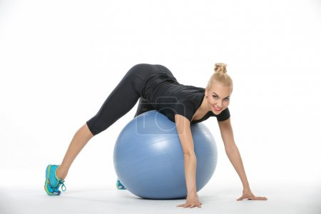 Sportive blonde lies on fitball