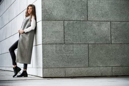 Photo for Attractive girl with beautiful hairstyle leans on the gray wall. She wears a gray coat without sleeves, a white blouse, dark jeans and black shoes. She holds the coat with her hands and looks the side. Her right leg is on the toe. Photographed from t - Royalty Free Image