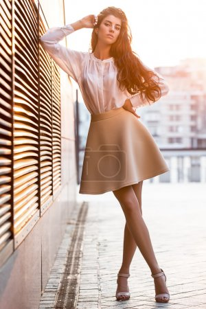 Photo for Stylish girl with beautiful hairstyle stands with crossed legs on the blurry urban background. She wears a white blouse, beige skirt and beige sandals. Right elbow leans on the lattice and the right hand leans on the head, left hand is on the waistba - Royalty Free Image