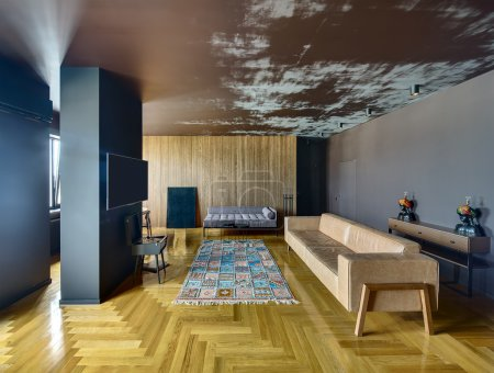Photo for Room in a modern style with various walls and parquet with colorful carpet on the floor. There is column with TV, vinyl player, sofas, chairs, picture, stand with candlestick, doors, rack with lamps. - Royalty Free Image