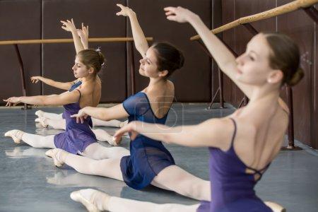 Photo pour Les jeunes ballerines sur la leçon de chorégraphie classique assis dans les fentes gracieusement lever les mains près de la barre . - image libre de droit