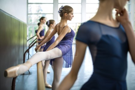 Photo pour Group of five young dancers trained in a dance class near the barre. Put your foot on the machine doing the workout. One dancer in focus, looking to the side. - image libre de droit