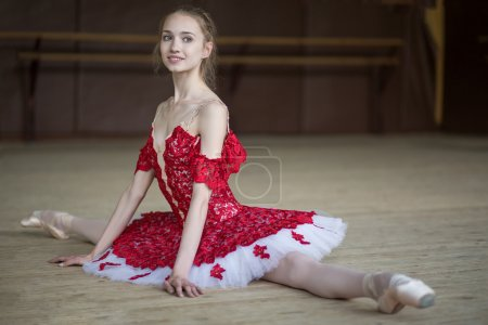 Ballerina sitting on the floor in the splits dress...