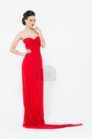 Photo pour Brunette sexy dans une robe de soirée rouge vif slinky isolée sur fond blanc en studio - image libre de droit