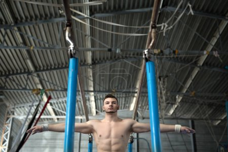 Athlete topless preparing to give gymnastic exercises on the une