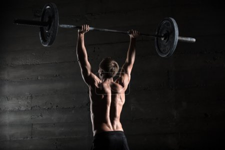 Photo for Portrait of a handsome athlete from behind. Athlete raises the barbell over your head. Studio shots in the dark tone - Royalty Free Image