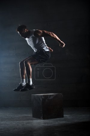 Photo pour Athlète a donné l'exercice. sauter sur la boîte. atterrissage de phase. photos de Studio dans le ton foncé - image libre de droit