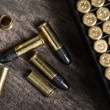 Постер, плакат: Scattering of small caliber cartridges on a wooden background