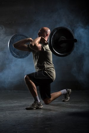 Photo for Bald athlete doing exercise with a barbell. Studio shot - Royalty Free Image