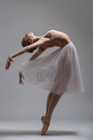 Graceful ballerina standing on toes bending the back