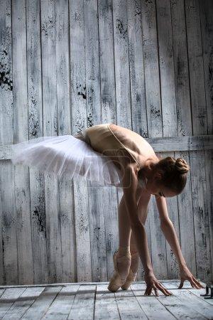 Ballerina dressed in white tutu makes lean forward