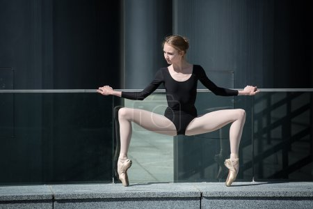 Young graceful ballerina in black bathing suit on a background o