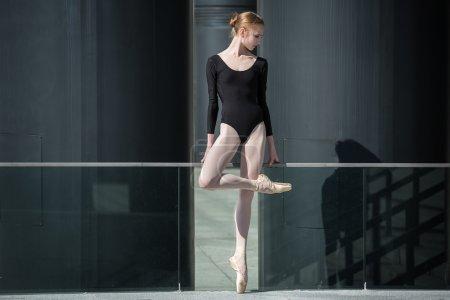 Photo pour Jeune ballerine gracieuse en maillot de bain noir sur fond de paysage industriel urbain. Instantané sur le territoire du stade moderne. Kiev - image libre de droit