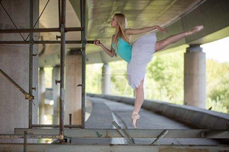 Ballerine gracieuse faisant des exercices de danse sur un pont en béton