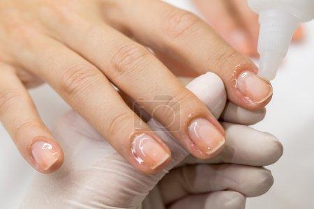 Photo pour Manucure de processus dans un salon de beauté. Mains du maître dans le client de clous polis de gants stériles - image libre de droit