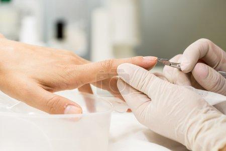 Photo pour Processus de manucure dans un salon de beauté. Mains du maître en gants stériles ongles polis client - image libre de droit