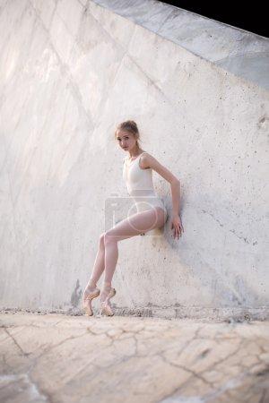 Slim dancer stands in a ballet pose