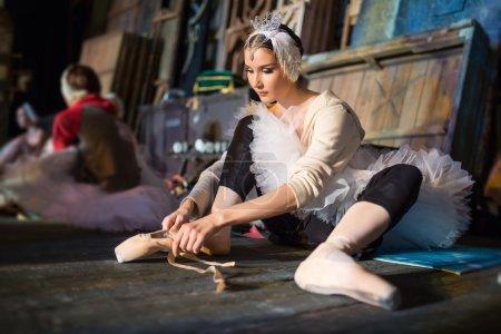 Photo pour Prima ballerina assise sur les coulisses du warm-up avant de monter sur scène pour un programme solo sur scène dans une performance de Swan Lake, voir le profil. Répétition - image libre de droit