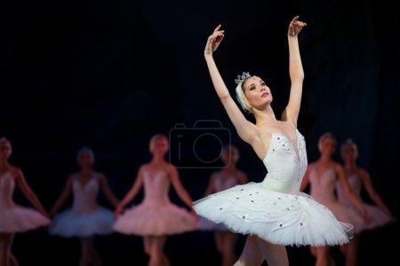 Photo pour Prima ballerina white swan sur scène danser gracieusement contre les autres danseurs. Le lac des cygnes Ballet, l'Opéra de Kiev, Ukraine - image libre de droit