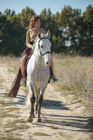 Beautiful girl riding on the white horse in a field