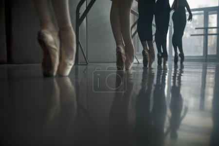Ballet dancers stands by the ballet barre.