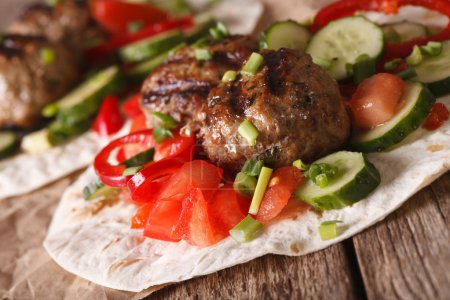 Meatballs with fresh vegetables on a tortilla close-up. horizont