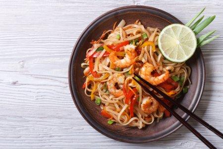 Photo pour Nouilles de riz aux crevettes et légumes en gros plan sur la table. vue de dessus d'une horizonta - image libre de droit
