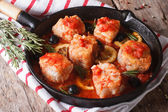 Fish fillet in tomato sauce in a pan and ingredients horizontal