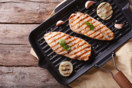 Chicken fillet with onion in a pan grill. horizontal top view