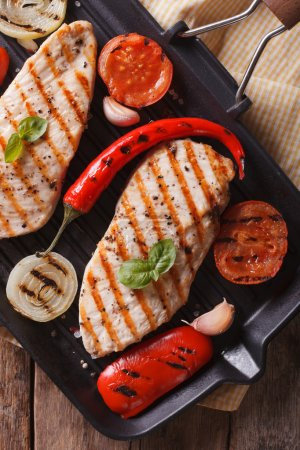 Chicken fillet with vegetables in pan vertical top view closeup