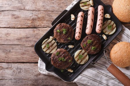 Burgers and sausages on a grill pan horizontal top view
