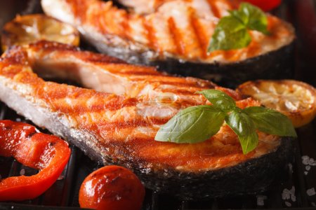 Photo for Delicious salmon steak and vegetables on the grill, macro. horizonta - Royalty Free Image