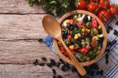Mexican vegetable salad in a wooden bowl, close-up horizontal to