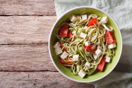 zucchini pasta with feta cheese and tomatoes horizontal top view