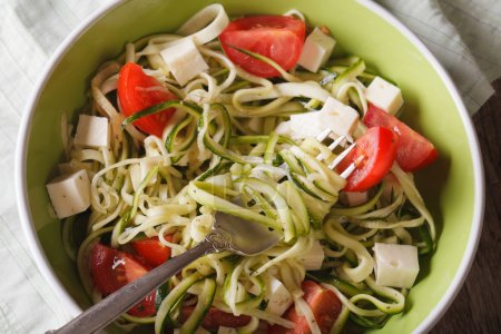 zucchini spaghetti with feta and tomatoes macro. horizontal top