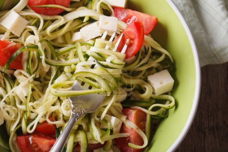 zucchini pasta with feta and tomatoes macro. horizontal top view