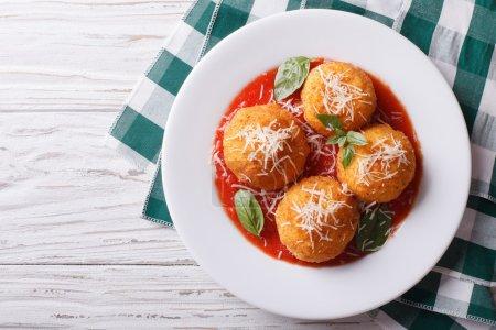fried arancini rice balls with tomato sauce. horizontal top view