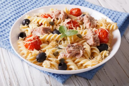 fusilli pasta with tuna, tomatoes and parmesan on the table. hor