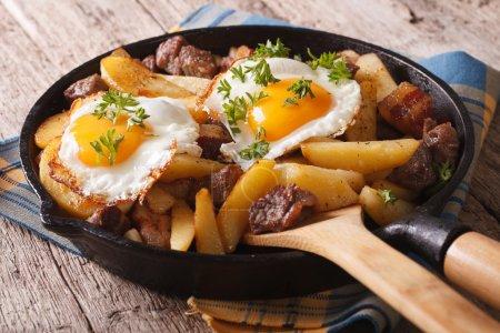 Photo pour Cuisine européenne : pommes de terre frites avec viande, bacon et œufs dans une casserole close-up. horizonta - image libre de droit