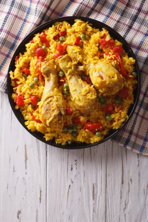 Spanish paella with chicken and vegetables. vertical top view