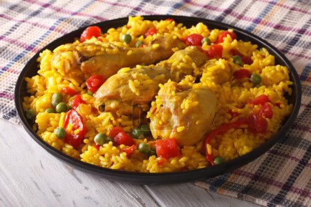 Spanish paella with chicken closeup on a plate. horizontal