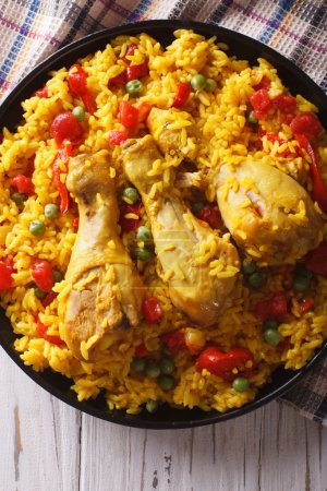 Spanish paella with chicken and vegetables closeup. vertical top