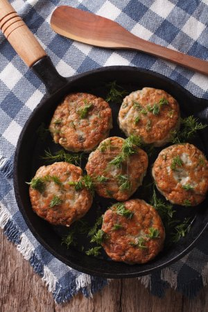 fish cakes with herbs in a pan. vertical top view