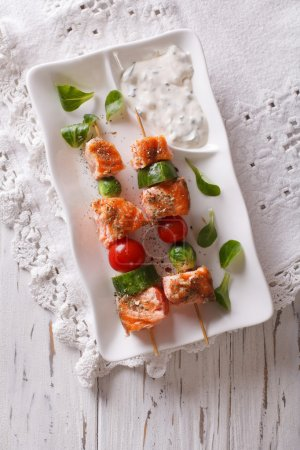Salmon kebab with vegetables on a plate. vertical top view