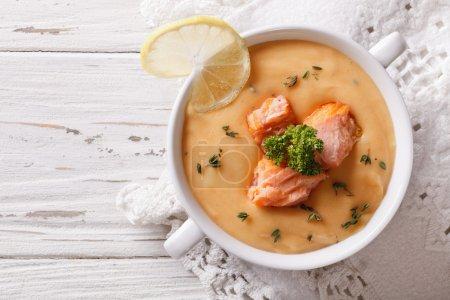 Salmon cream soup with lemon on the table. horizontal top view