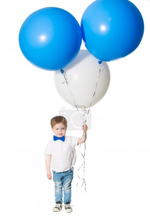 Little boy holding a bunch of colored large balloons