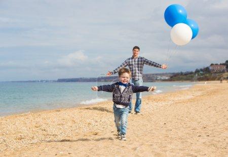 Photo pour Famille avec de grands ballons jouant sur la plage - image libre de droit